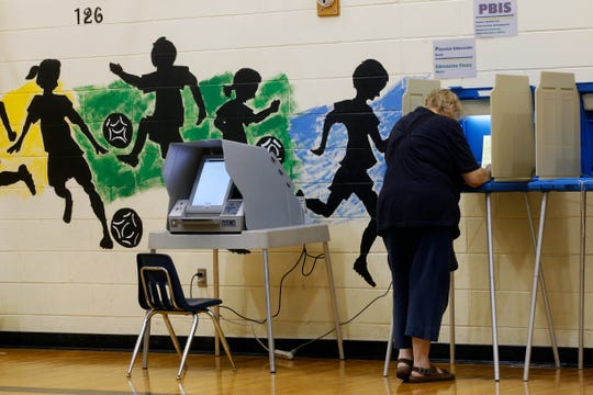 A woman casts her vote in the gym at Wards 123 and 124 at Fratney Street School on Tuesday in Milwaukee.