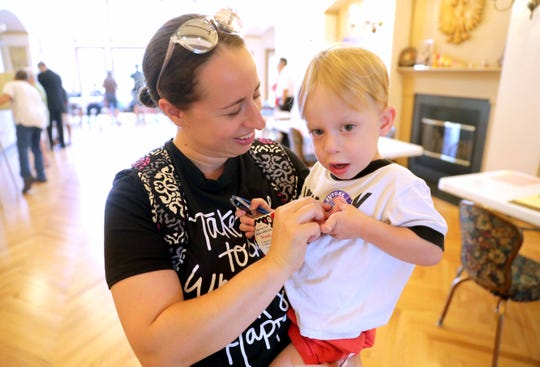 """Kate Krueger puts a """"future voter"""" sticker on her 2-year-old son Henry after she voted at The Polish Center of Wisconsin in Franklin."""
