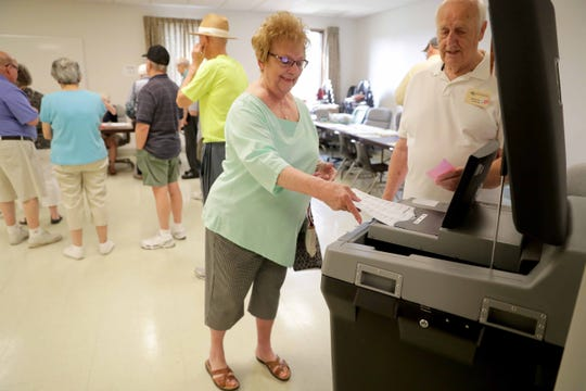 Arline Jasinski feeds her ballot as poll worker Richard Koehler looks on at Franklin City Hall.