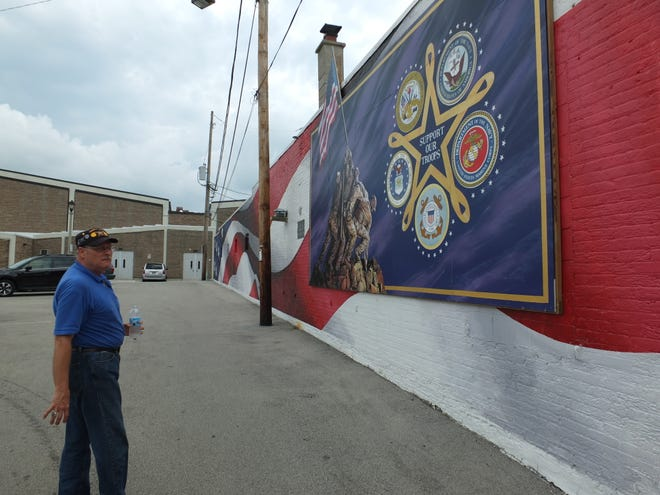 Ray Grabowski stands by the mural which has been damaged by cars backing into the wall. The American Legion building is over 100 years old and is in need of repair.