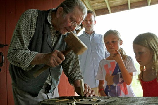 Old World Wisconsin interpreter Bob Levinson, of East Troy, shows (from left) Dave, Erin and Caty Hughes of Madison how wooden nails were made.