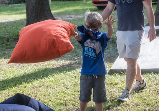 Bryson Allen, 6, throws a giant corn hole bag. Shindig, a free concert and outdoor gathering that was also a fundraiser for Child Protect, Children's Advocacy Center, was held July 29, 2018, at Montgomery's Winter Place in Historic Cottage Hill.