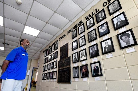 John Oliver looks at a wall of historic photos as he works the desk the Cleveland Avenue YMCA in Montgomery, Ala., on Tuesday August 14, 2018.