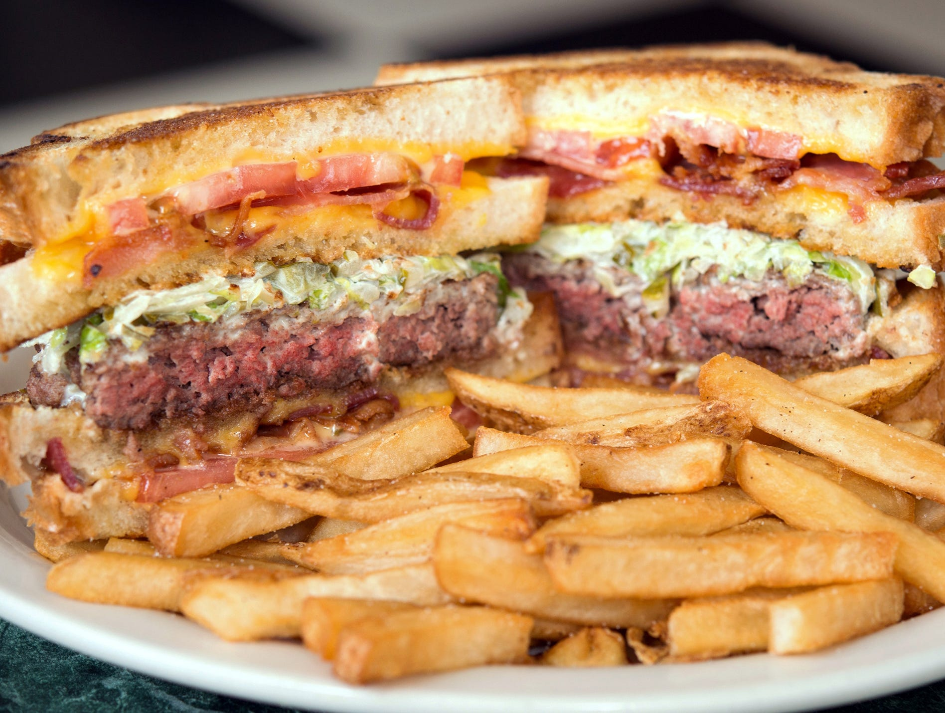 The Vortex Burger at Metro Diner features a half-pound Angus beef patty topped with lettuce slaw in between two grilled cheese sandwiches stuffed with American cheese, ripe tomatoes and hickory smoked bacon.