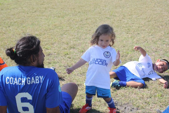 Coach Gabriel Mejia plays with ISSA's youngest players, Raymond Tepochtli Mejia Perkins and Axel Chavarria.