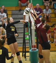 Watkins Memorial's Jenna Lucas spikes the ball at Newark defenders during a scrimmage. Newark Catholic volleyball hosted preview scrimmages on Monday, Aug. 13, 2018.