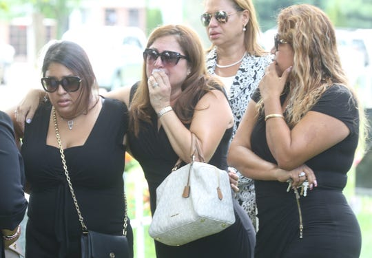 Mourners react as music is played at the gravesite of Zaida Polanco.