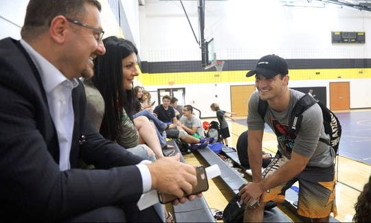Tony Asatrian and his father Harry and mother Deanna during a break as they attend a wrestling scrimmage at River Dell High School this summer.