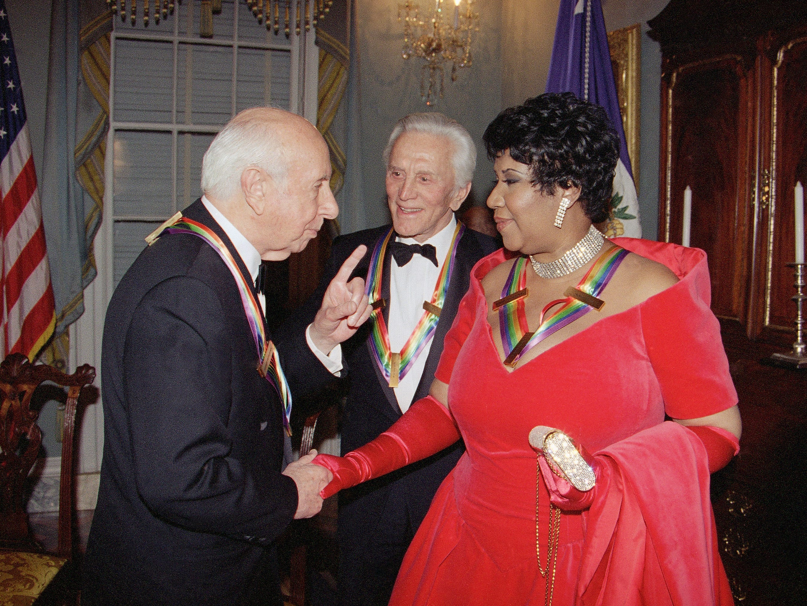Singer Aretha Franklin listens to composer Morton Gould, as actor Kirk Douglas looks on following a dinner at the State Department in Washington  Saturday, Dec. 3, 1994. The dinner was held to honor them as recipients of the Kennedy Center Honors of 1994. Also honored were songwriter Pete Seeger and Director Harold Prince.