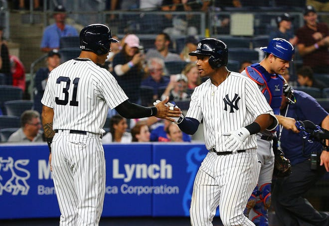 New York Yankees third baseman Miguel Andujar (41) is congratulated by center fielder Aaron Hicks (31) after hitting a two run home run against the New York Mets during the eighth inning at Yankee Stadium.