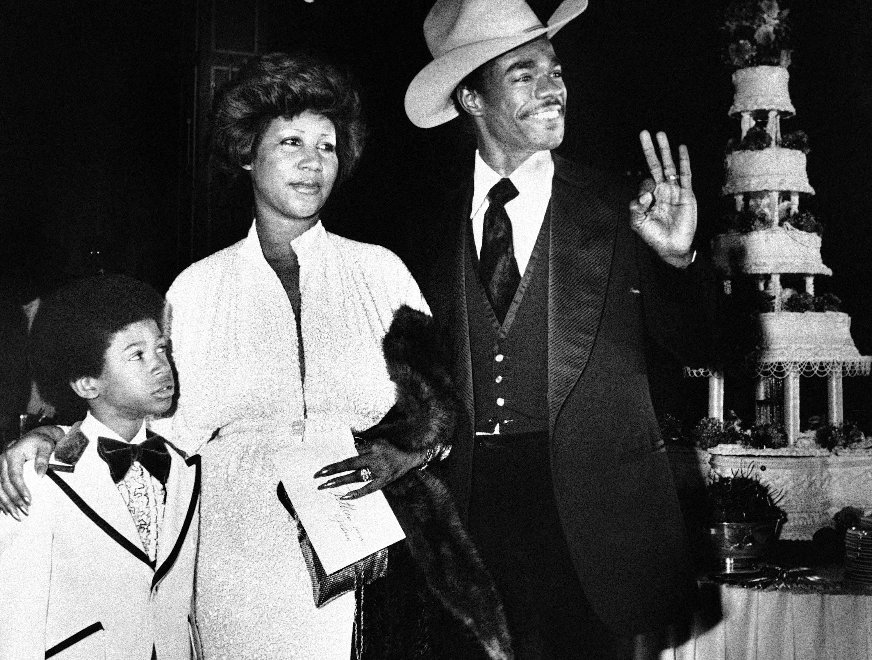 Aretha Franklin and her new husband, Glen Turman, arrive at a Los Angeles hotel, April 17, 1978 for their wedding reception. Turman signals his okay and pleasure at the reception as Kecalf (cq) 8, Aretha's son by a previous marriage looks on. The couple married recently,had planned a reception at her Beverly Hills home on Saturday but the party was rained out, and moved to the hotel for the Sunday party. (AP Photo/Doug Pizac)
