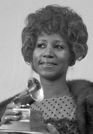 """Queen of soul Aretha Franklin holds her Grammy Award for Best Rhythm and Blue performance of the song """"Bridge Over Troubled Waters,"""" March 13, 1972, in New York. (AP Photo/Dave Pickoff)"""