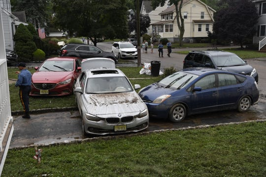 Cars are piled up on Harrison street in Little Falls after a flood ravaged the neighborhood on Sunday.