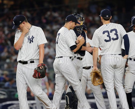 New York Yankees starting pitcher A.J. Cole, left, leaves during the seventh inning of a baseball game against the New York Mets Monday, Aug. 13, 2018, in New York.