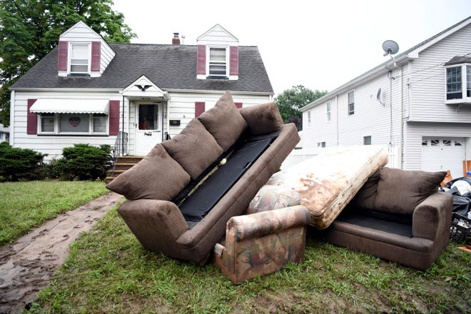 Damaged furniture sits on Jackson street after the neighborhood in Little Falls experienced severe flooding.