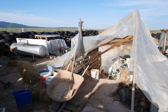 Various items litter a squalid makeshift living compound in Amalia, N.M., on Friday, Aug. 10, 2018, where five adults were arrested on child abuse charges and remains of a boy were found. The remains, which haven't been positively identified, may resolve the fate of Abdul-ghani Wahhaj, a missing, severely disabled Georgia boy. Eleven other children were found at the compound during a raid last week.