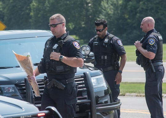 A citizen stopped and gave flowers to honor the victim of the hit and run.A Dearborn Heights officer places the flowers in his car.