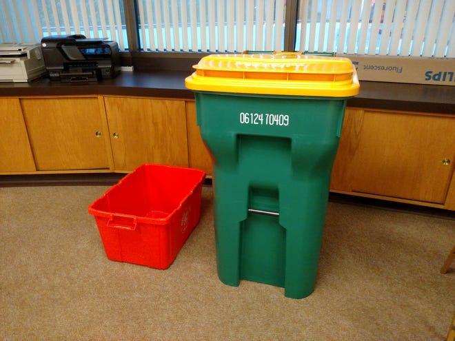 An 18-gallon recycling bin, left, next to a 64-gallon recycling cart.