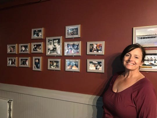 Carolyn Ciungan stands next to photos of family photos from years gone by at the Village Bar.