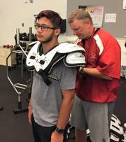 Clarenceville coach Ryan Irish (right) makes sure junior Bryce Olney's shoulder pads fit properly.