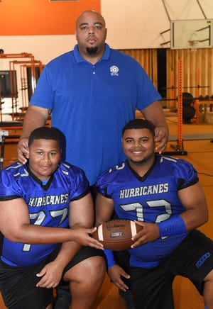 North Central head football coach Jacobi Thierry stands with two starters for the Hurricanes: O'Trention Morrison (77) and James Vaughn (72).