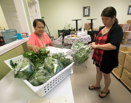 Rosita Graycochea and Maricel Carreon prepare fresh greens for resale Tuseday at the Kabayan Grocery Store on New Warrington Road.