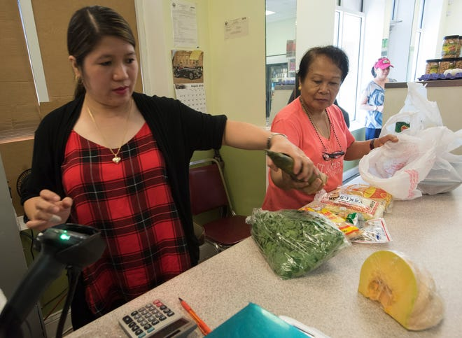 Maricel Carreon and Rosita Graycochea add up a customer's food order Tuesday at the Kabayan Grocery Store on New Warrington Road.