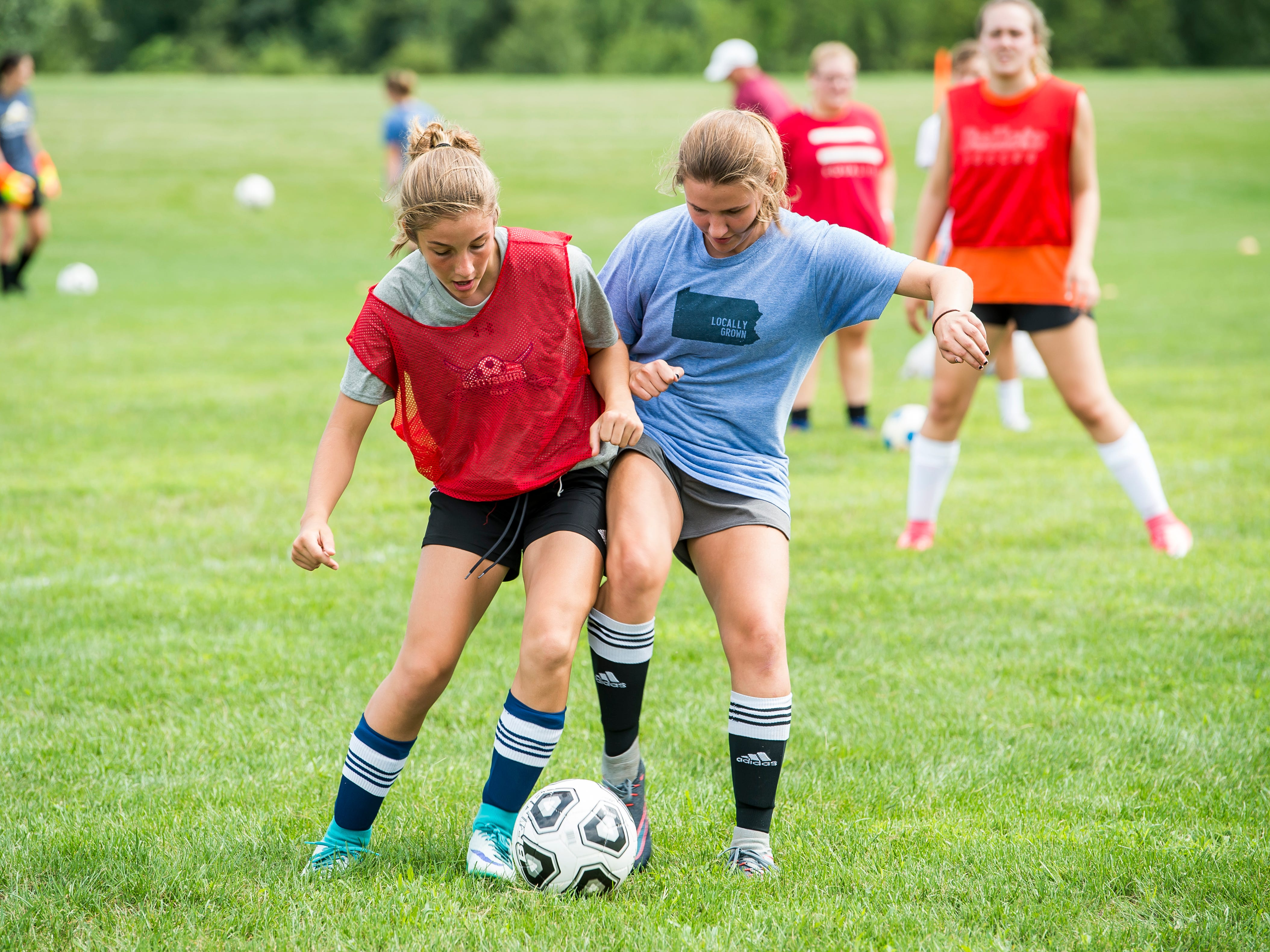Gettysburg girls soccer players Rachel McKinney, left, and Sam Shafer battle for the ball during the first day of fall sports practice on Monday, August 13, 2018.