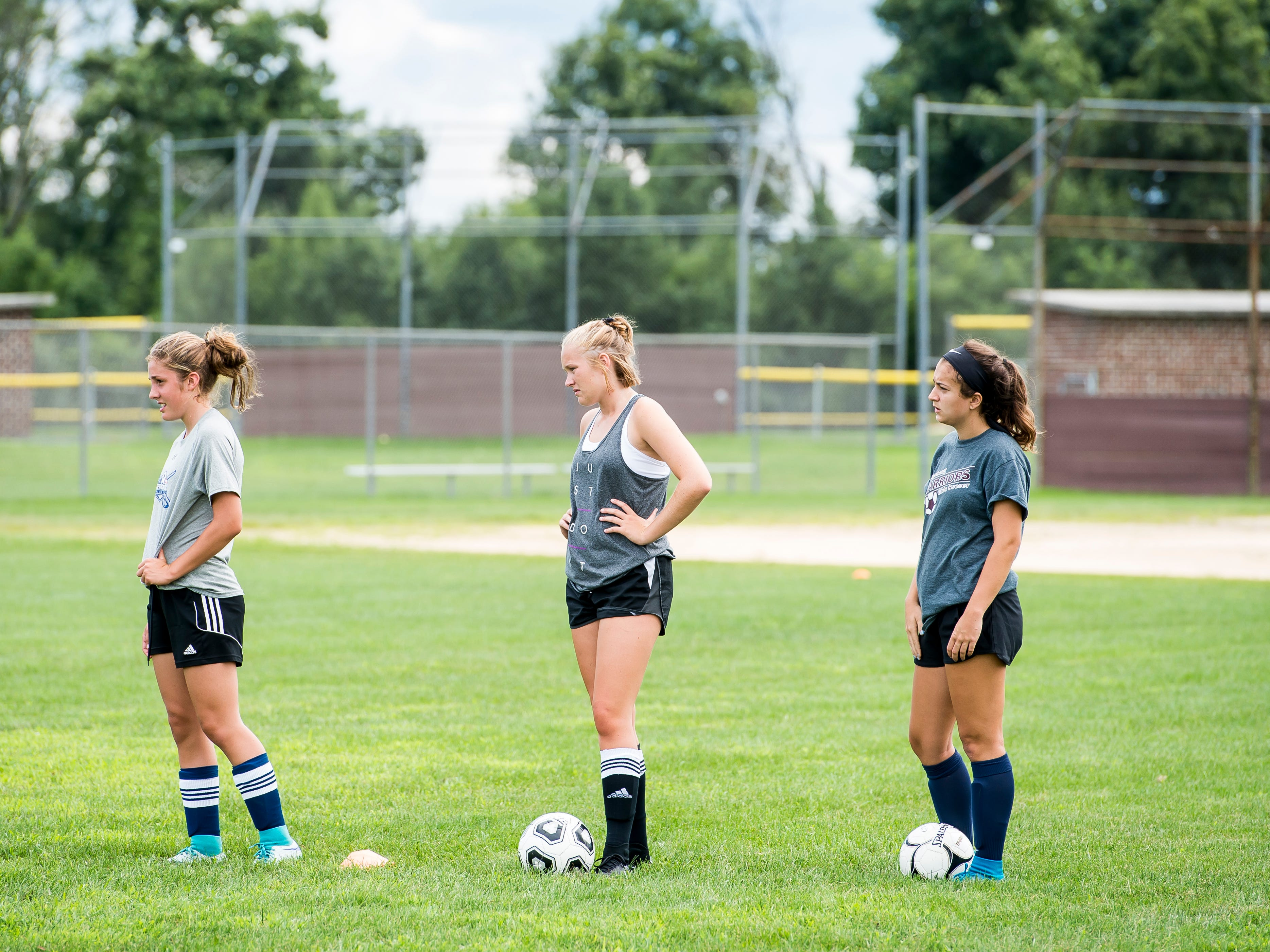(From left) Gettysburg's Rachel McKinney, Lily Crowner and Olivia Sica listen to a coach during the first day of fall sports practice on Monday, August 13, 2018.