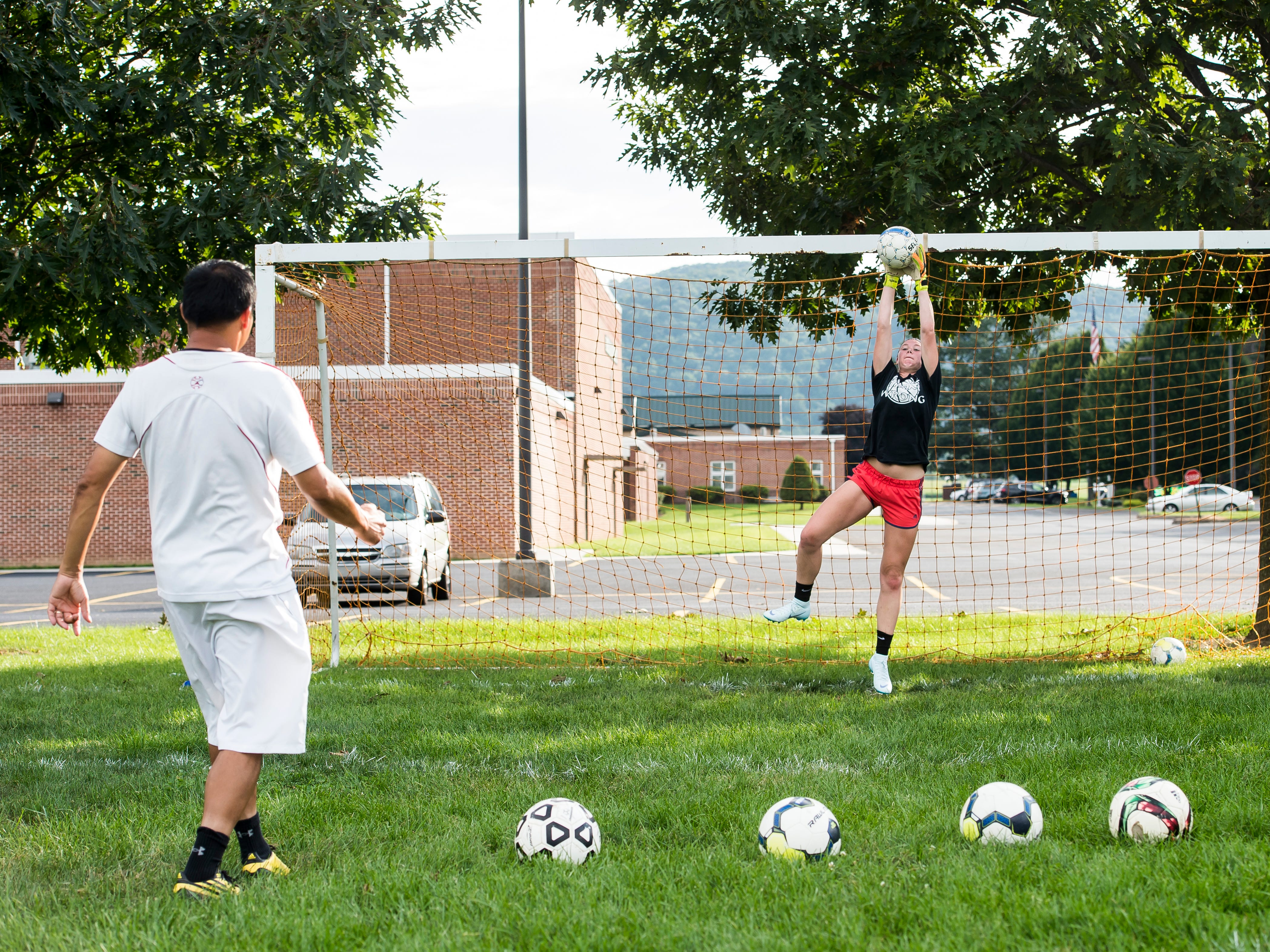 Fairfield junior goalkeeper Haley Bolin blocks a shot from the foot of coach Phomma Phanhthy during a rapid fire drill on the first day of fall sports practice on Monday, August 13, 2018.