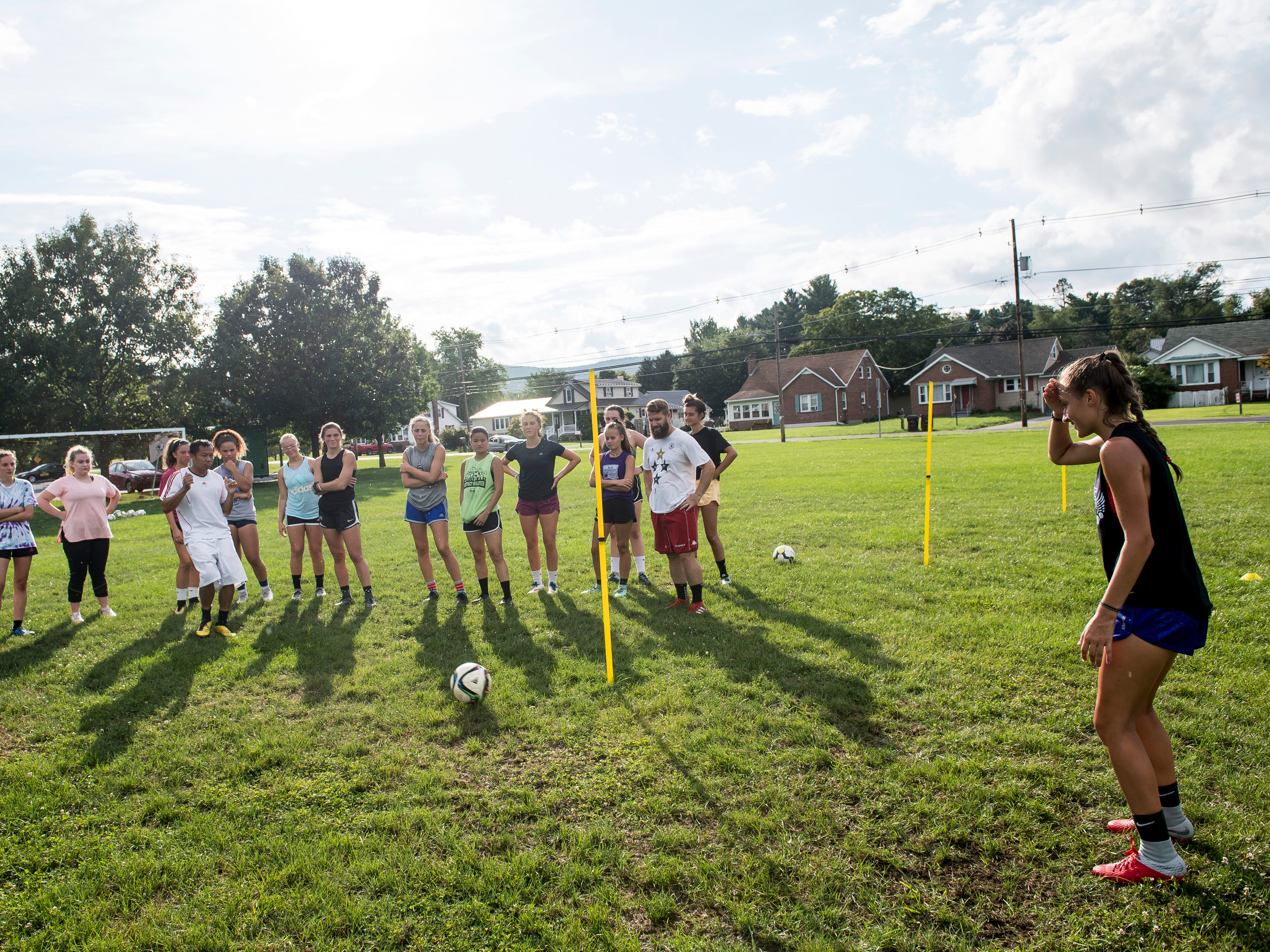Fairfield girls soccer head coach Phomma Phanhthy, left, kicks the ball to Rio Strosnider while demonstrating a drill during the first day of fall sports practice on Monday, August 13, 2018.
