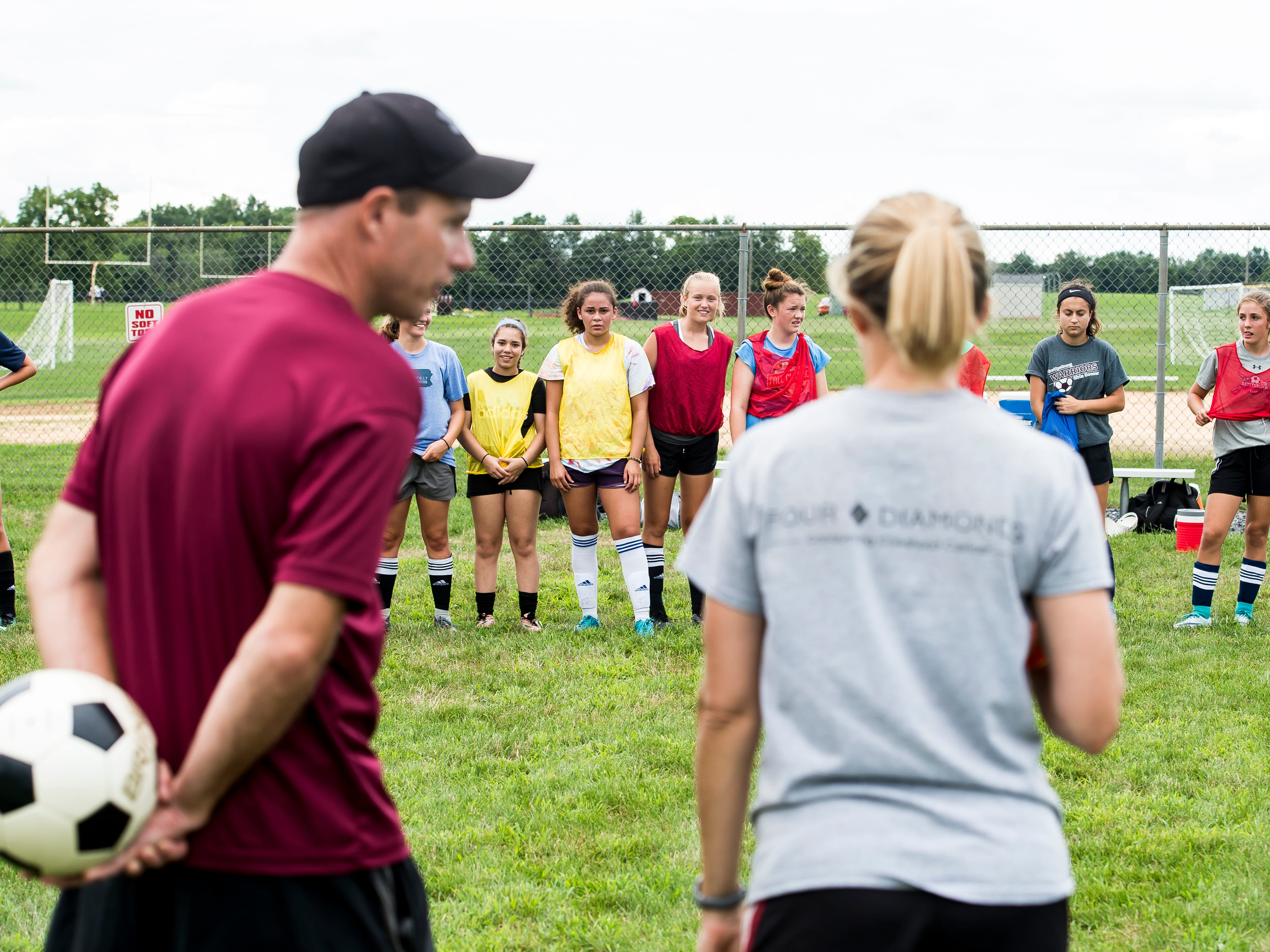 Gettysburg girls soccer players stand in a line as head coach Josh Fissel and assistant coach Kathy Reinert talk during the first day of fall sports practice on Monday, August 13, 2018.