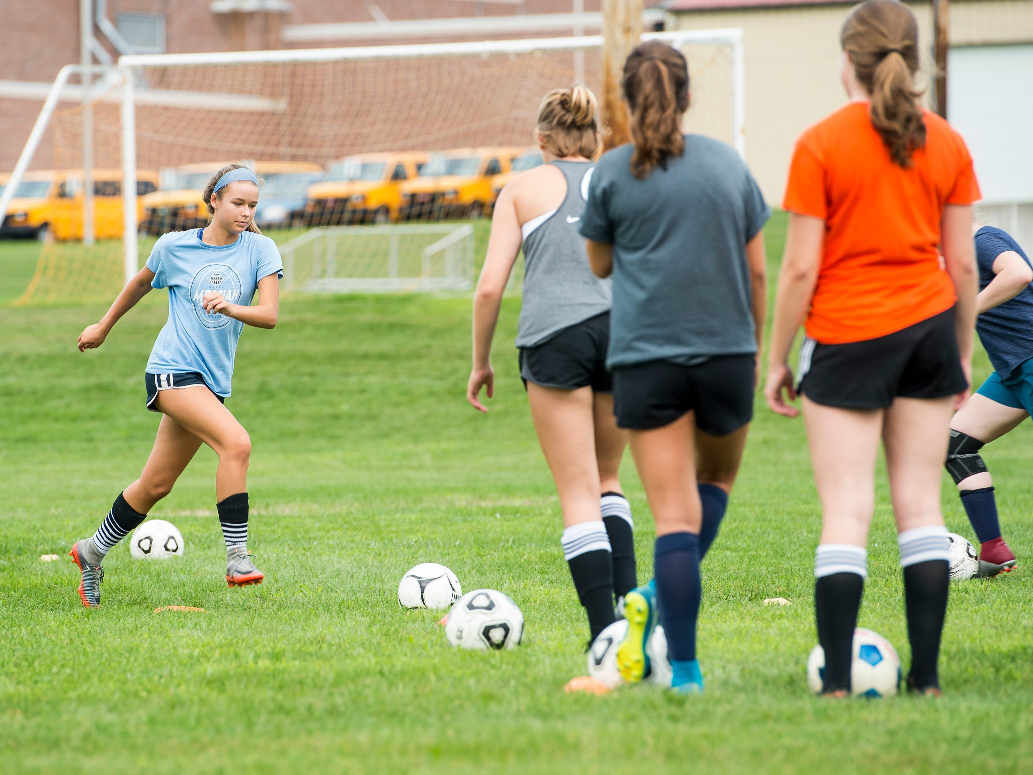 Gettysburg's Lora Bertram, left, prepares to kick a soccer ball during the first day of fall sports practice on Monday, August 13, 2018.