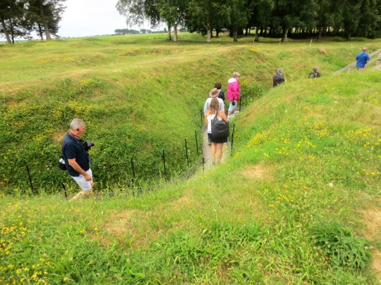 Visitors walk through the trenches at the Somme battlefield in France.