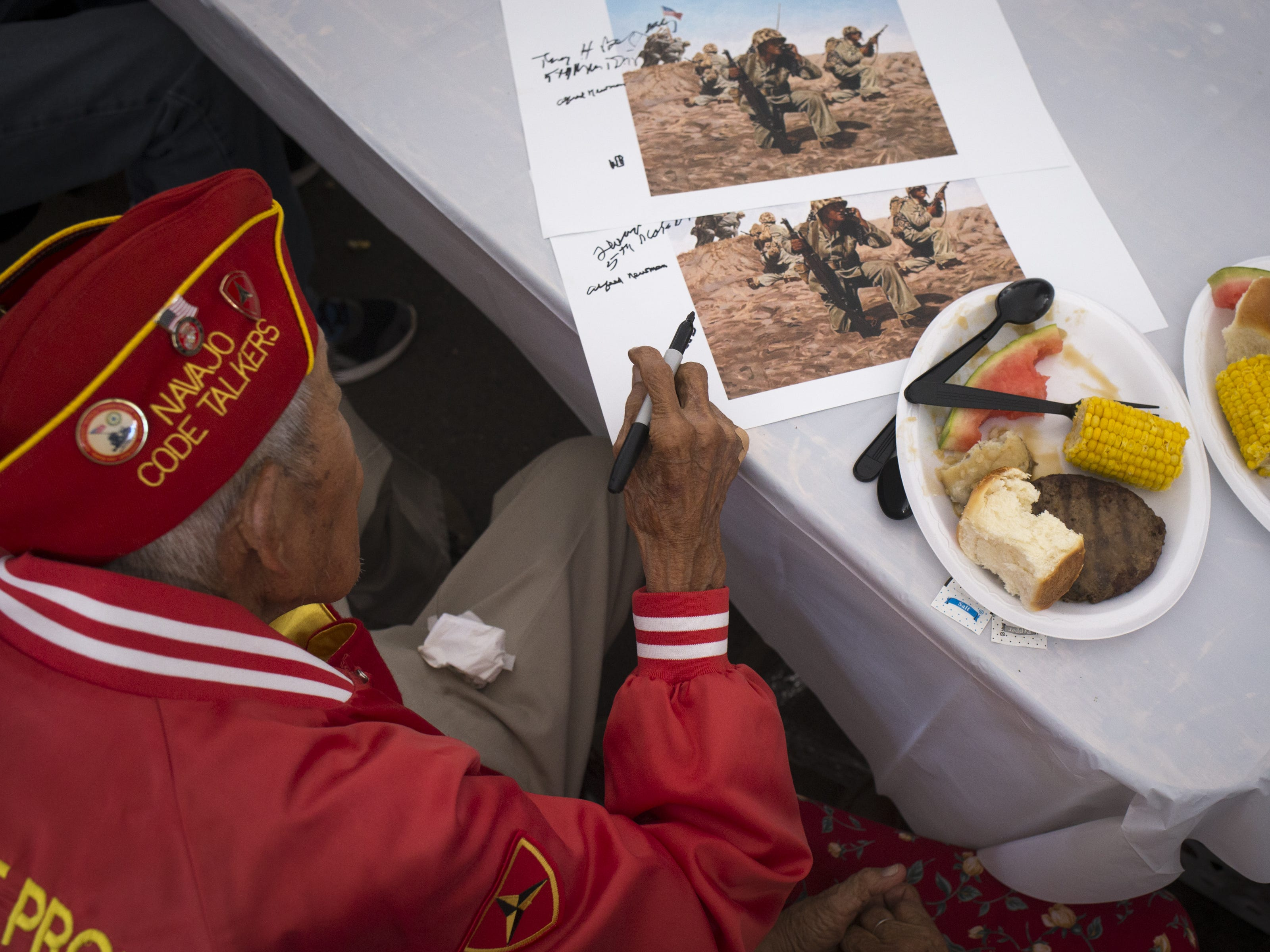 Navajo Code Talker Alfred K. Newman signs a poster after the Navajo Nation Code Talkers Day ceremony on Aug. 14, 2018, at the Veterans Memorial Park in Window Rock.
