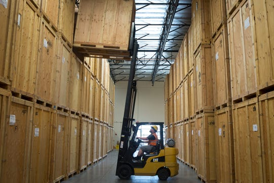 Warehouse supervisor Sean Medley moves a storage box in the warehouse Aug. 7, 2018, at Muscular Moving Men in Phoenix.