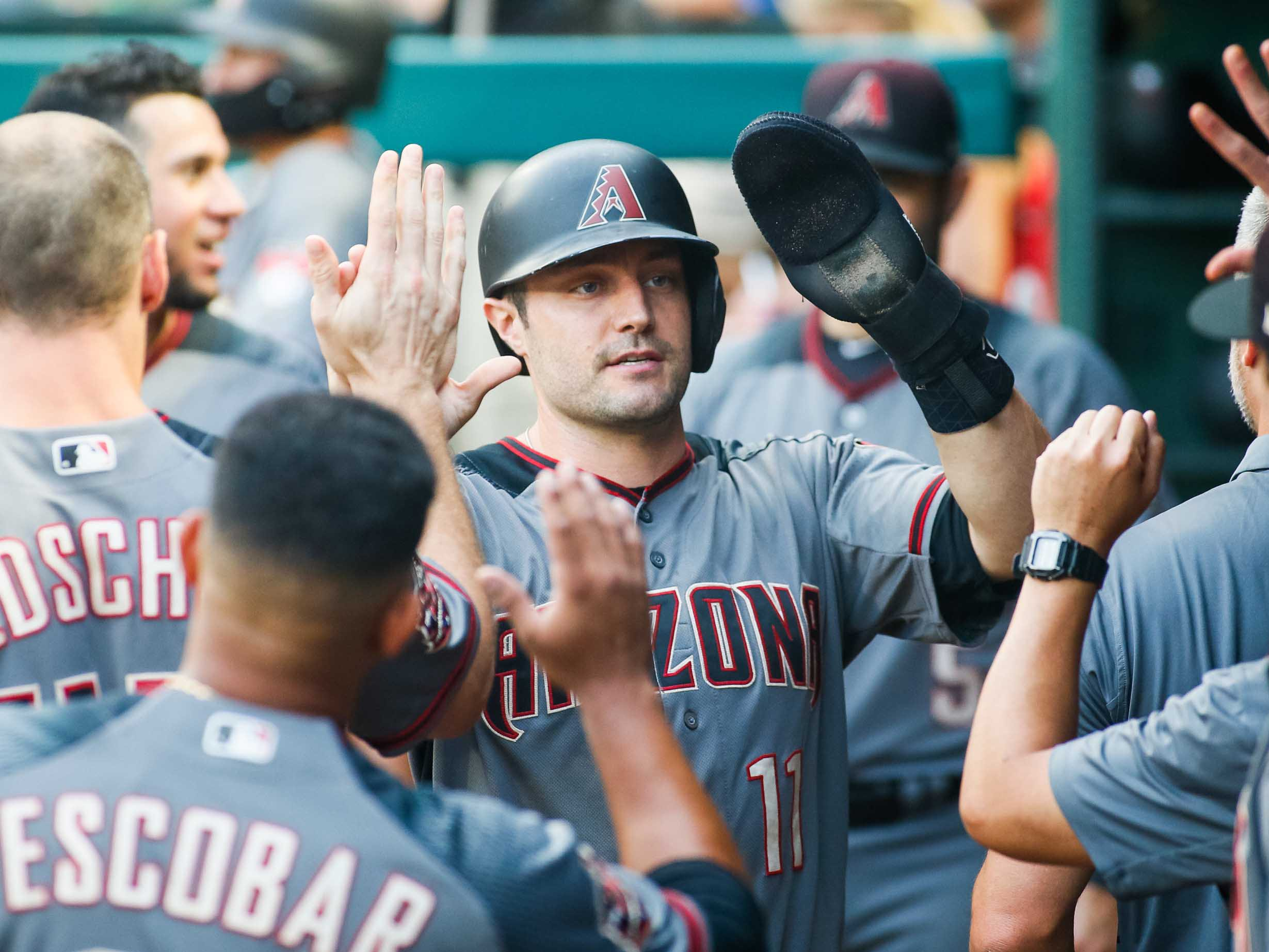 Aug 13, 2018; Arlington, TX, USA; Arizona Diamondbacks center fielder A.J. Pollock (11) is greeted in the dugout after scoring in the first inning against the Texas Rangers at Globe Life Park in Arlington. Mandatory Credit: Ray Carlin-USA TODAY Sports