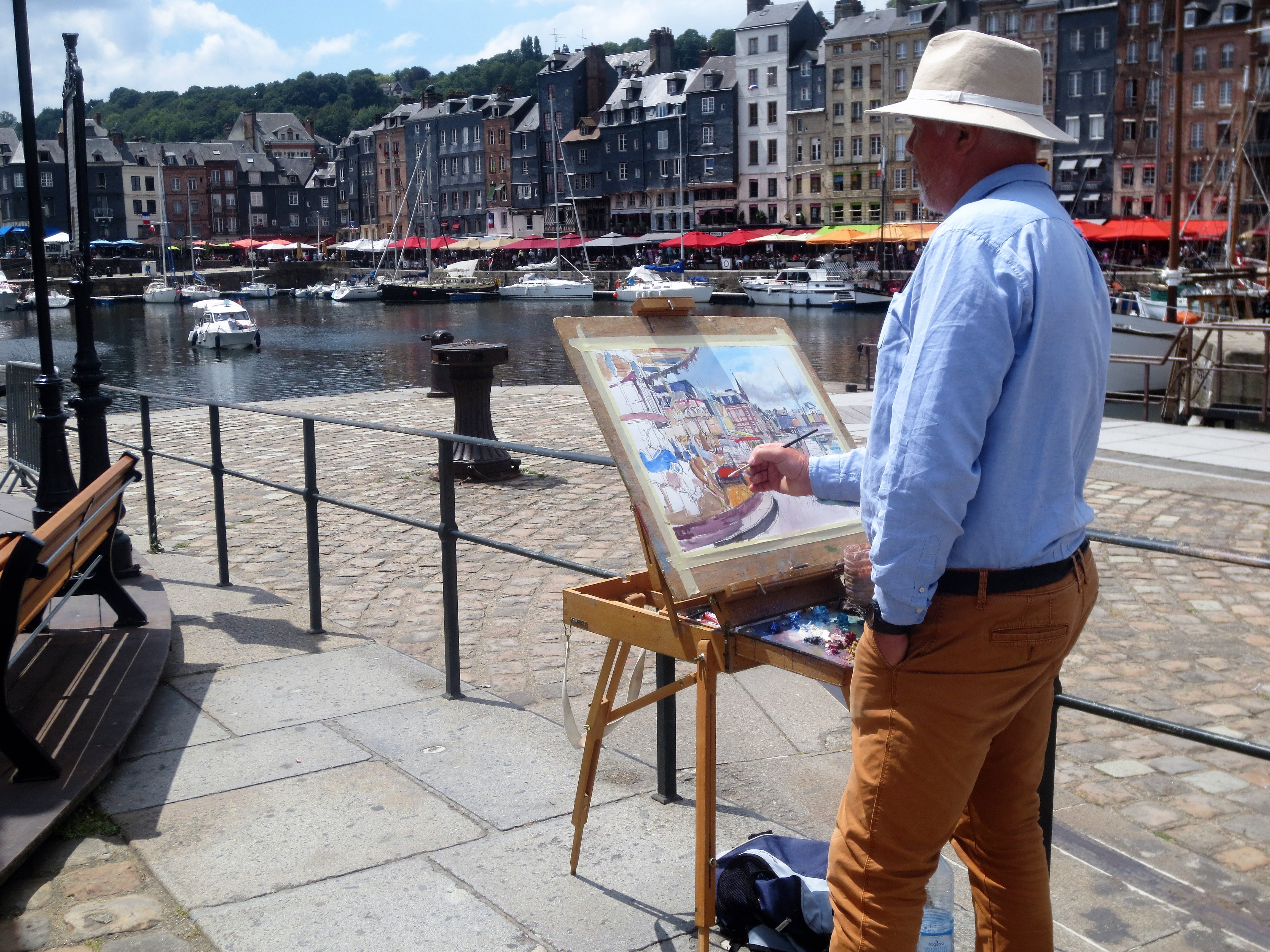 An artist paints the picturesque harbor in Honfleur, France, near where the Seine River empties into the English Channel.