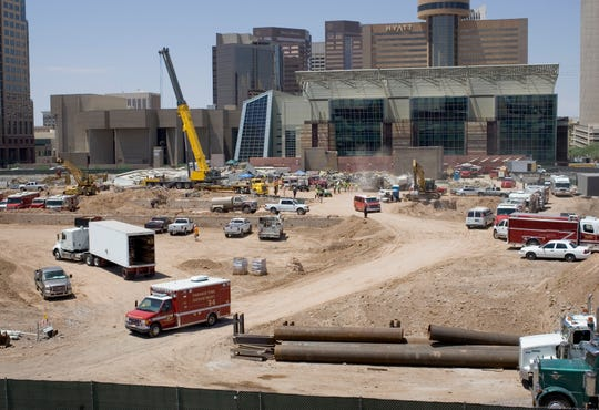 Rescue workers move seriously injured construction worker Casey Johansen who was trapped by a 200-foot wall of concrete that collapsed during a demolition project at the Phoenix Convention Center on Aug. 8, 2006.