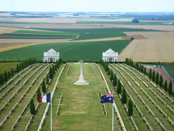 The flags of France (left) and Australia fly over the Normandy countryside in a military cemetery at the site of the World War I Battle of the Somme.