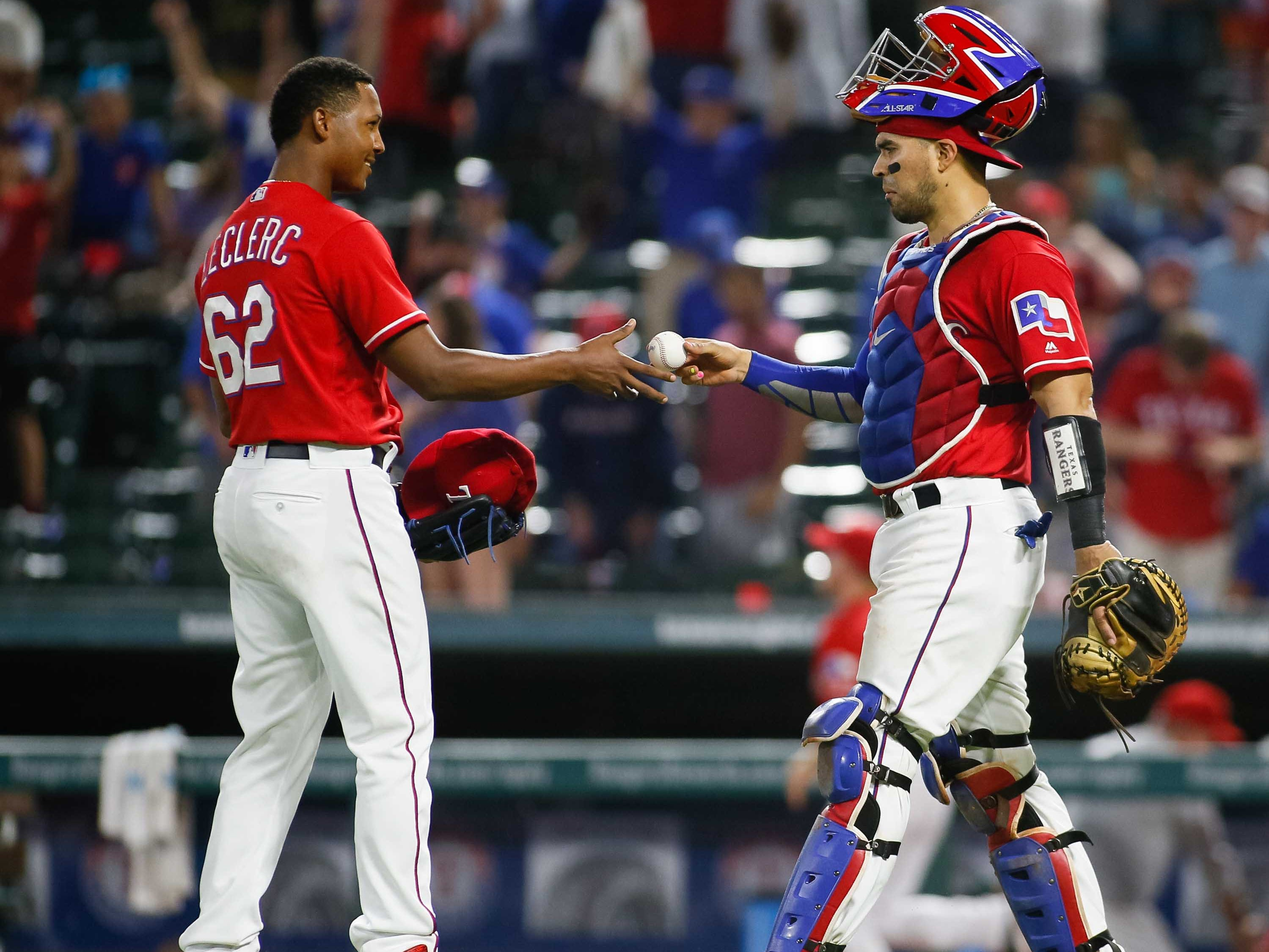 Aug 13, 2018; Arlington, TX, USA; Texas Rangers catcher Robinson Chirinos (61) hands relief pitcher Jose Leclerc (62) the ball after recording the final out against the Arizona Diamondbacks at Globe Life Park in Arlington. Mandatory Credit: Ray Carlin-USA TODAY Sports
