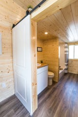 View toward bathroom at opposite end; note barn door hardware above opening to bathroom, which will boast a walk-in shower at completion.