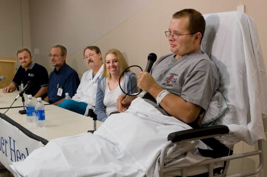 Casey Johansen speaks at a news conference at Banner Good Samaritan Medical Center in Phoenix. Looking on are Joe Pongratz (from left) of Pongratz Orthotics and Prosthetics, Bob Heisler of the hospital's rehabilitation staff, trauma surgeon Dr. Corey Detlefs, and Johansen's wife, Bethany.