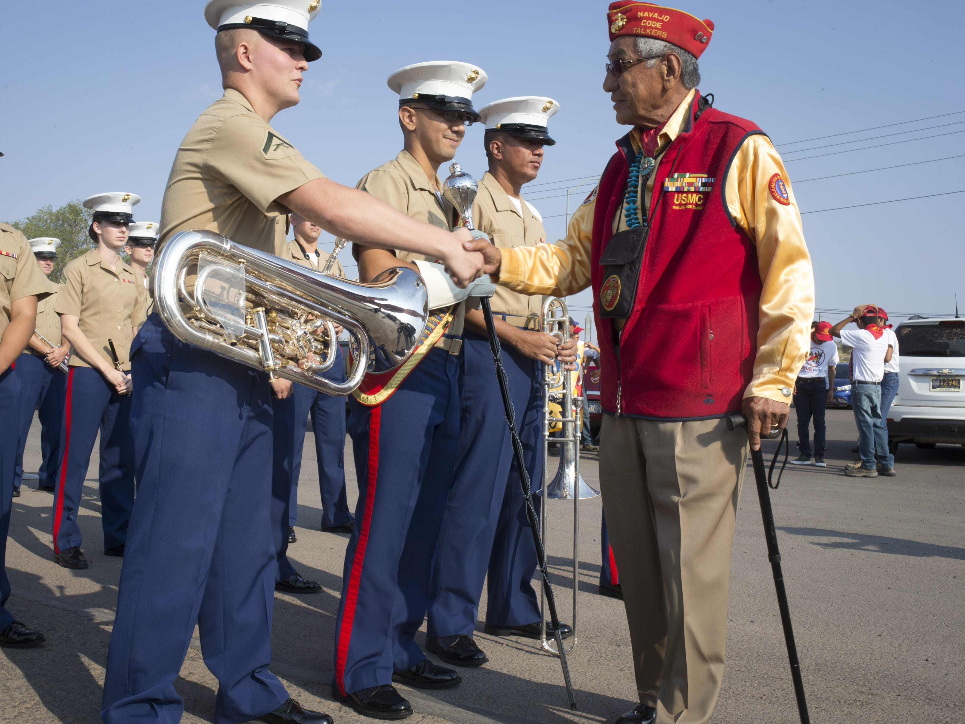 Navajo Code Talker Peter MacDonald greets members of the Marine Forces Reserve Band before the start of the Navajo Nation Code Talkers Day parade on Aug. 14, 2018, at the Navajo Nation Fairgrounds in Window Rock.