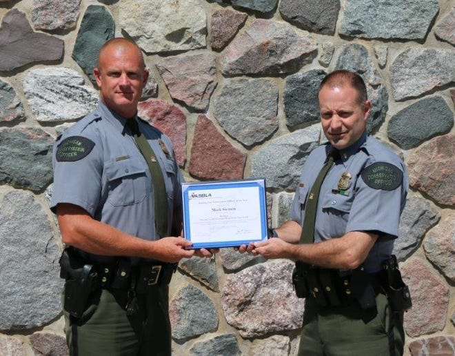 Conservation Officer Mark Sieman, left, receives an award from DNR Lt. Tom Wanless. Sieman is the MIchigan Boating Law Enforcement Officer of the Year for 2017.
