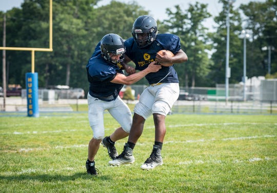Port Huron Northern linebacker Austin Eagle, left, grabs at middle linebacker John Young during a defensive drill Tuesday, Aug. 14, 2018, during a practice at Port Huron Northern High School.