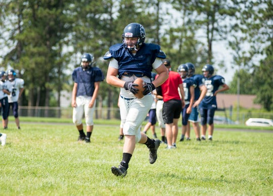Yale linebacker Travis Miracle runs with the ball during warmup Tuesday, Aug. 14, 2018, during practice at Yale High School.
