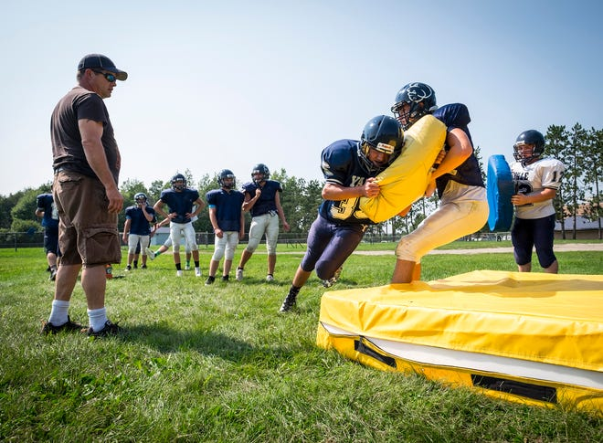 Yale junior varsity linebacker Dylan McCormick goes down while grabbing a pad held by split end Mark Donnellon during practice Tuesday, Aug. 14, 2018, at Yale High School.