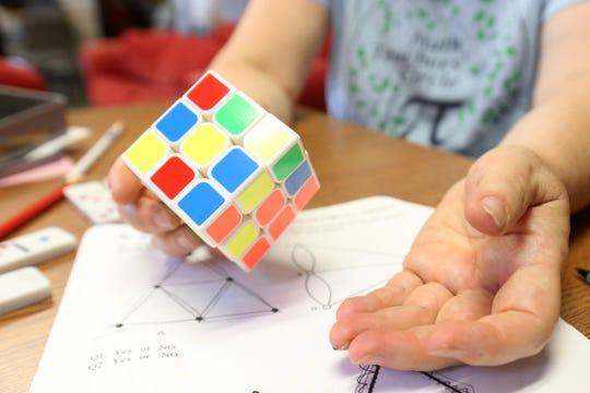 Lauren Rose holds a Rubik's Cube over a packet of math puzzles in the Mathematics department lounge at Bard College on August 10, 2018.