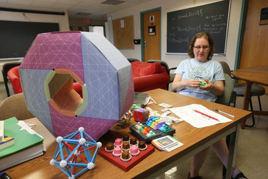 Surrounded by math-based puzzles and activities, Lauren Rose, a math professor at Bard College, works on a Rubik's Cube in the math department lounge at Bard College on August 10, 2018. Rose started the Bard Math Circle in 2008 which encompasses various activities to grow appreciation and understanding of mathematics.